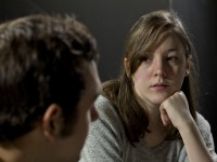 Young woman listening to man's testimony at support group